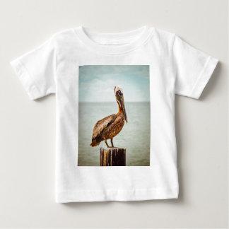 Pelícano bonito encaramado sobre el océano camiseta de bebé