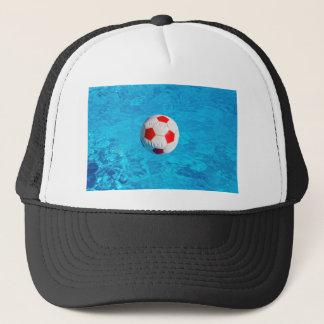 Pelota de playa que flota en piscina azul gorra de camionero
