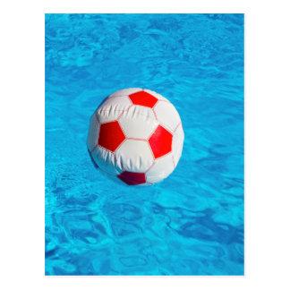 Pelota de playa que flota en piscina azul postal