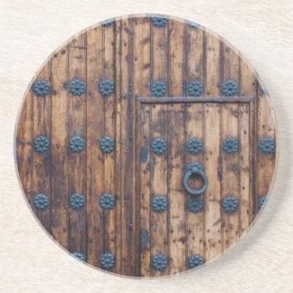 Pequeña puerta vieja dentro de puertas grandes posavasos de arenisca