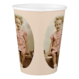 Pequeño chica rubio del vintage en la taza de vaso de papel