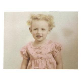 Pequeño chica rubio del vintage en libreta rosada