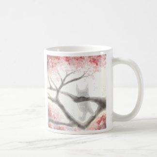 Pequeño gato gris en una taza del árbol