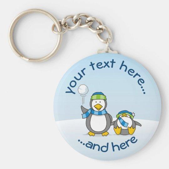 Pequeño pingüino que consigue una bola de la nieve llavero redondo tipo chapa