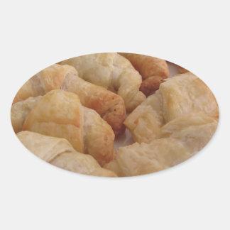 Pequeños croissants salados hechos en casa pegatina ovalada