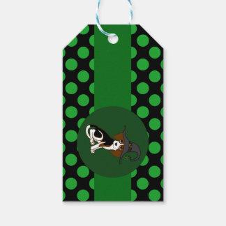 Perrito del beagle con el gorra de la bruja y los etiquetas para regalos