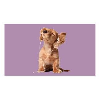 Perrito joven que escucha la música en los tarjetas de visita