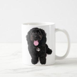 Perrito negro que mira para arriba taza de café