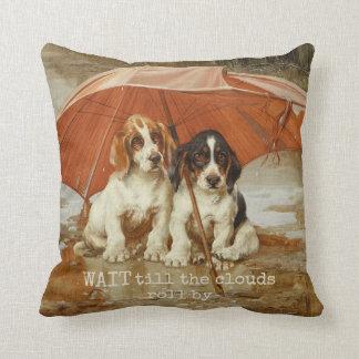 Perritos del perro de afloramiento debajo del cojín decorativo