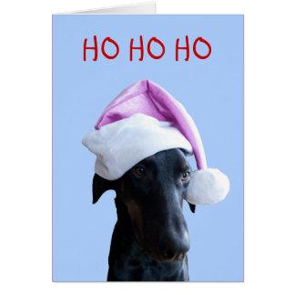 Perro divertido con la tarjeta de Navidad rosada