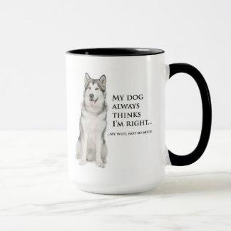 Perro esquimal divertido contra la taza de la
