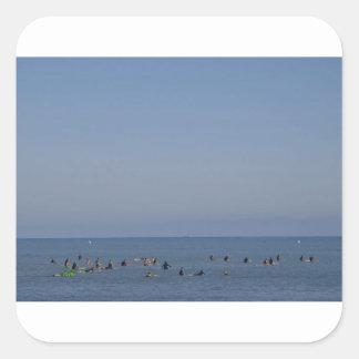 personas que practica surf que esperan una onda pegatina cuadrada