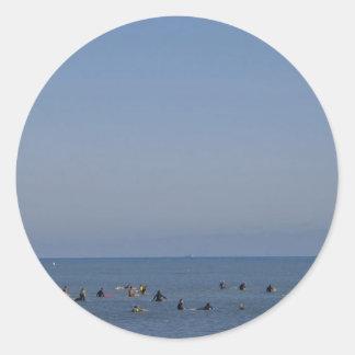 personas que practica surf que esperan una onda pegatina redonda