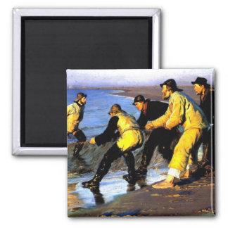 Pescadores que acarrean la red en la playa del imán