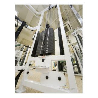 Pesos en una máquina del ejercicio en gimnasio, án tarjetas postales