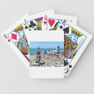 Piedras apiladas de la playa en el mar azul baraja de cartas bicycle