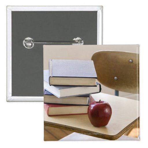 Pila de libros, de manzana, y de escritorio de la  pins