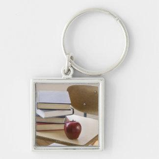 Pila de libros, de manzana, y de escritorio de la  llaveros