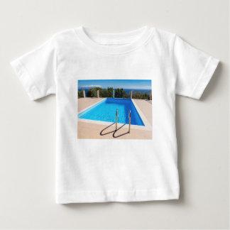 Piscina azul con pasos en el mar camiseta de bebé