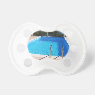 Piscina azul con pasos en el mar chupete