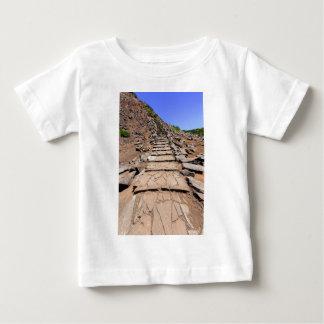 Pista de senderismo que lleva a la montaña en camiseta de bebé