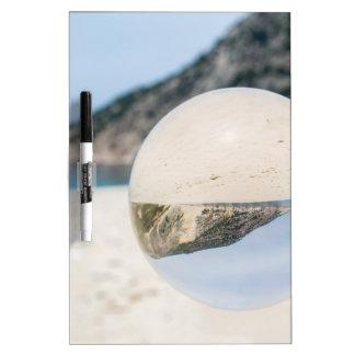 Pizarra Blanca Bola de cristal en la playa griega arenosa