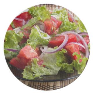 Placa del primer con una ensalada de la rebanada platos