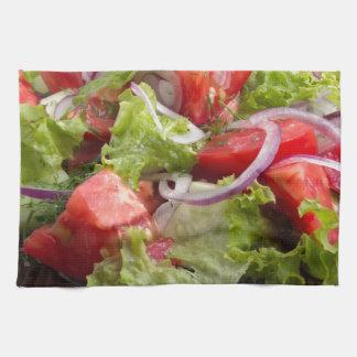 Placa del primer con una ensalada de la rebanada toallas de cocina