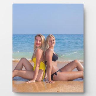 Placa Expositora Dos chicas se sientan en la playa cerca de sea.JPG