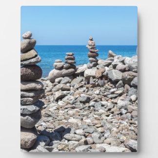 Placa Expositora Piedras apiladas de la playa en el mar azul