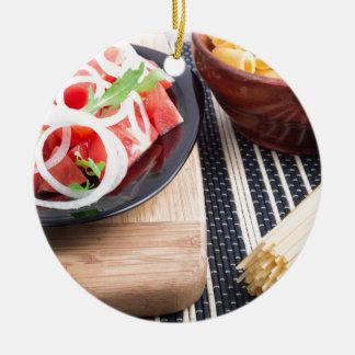 Placa negra con la ensalada fresca de los tomates, adorno de cerámica