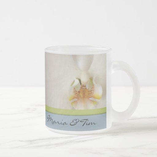 Plantilla blanca de la orquídea con acento azul y  taza cristal mate