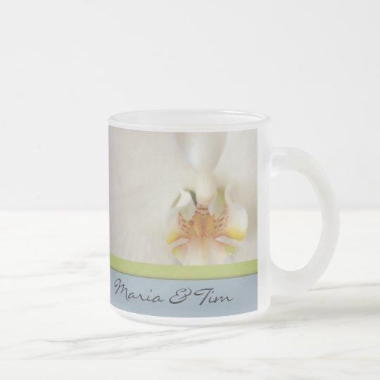 Plantilla blanca de la orquídea con acento azul y taza de cristal esmerilado