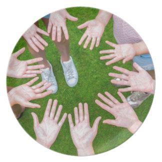 Plato Diez brazos de niños en círculo con las palmas de