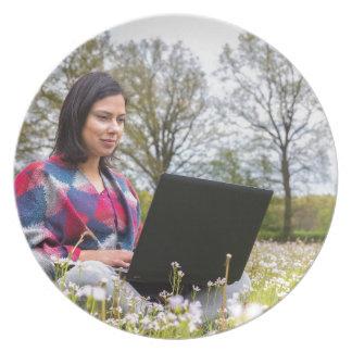 Plato La mujer se sienta con el ordenador portátil en