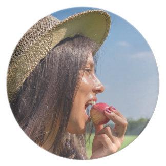 Plato Mujer con el gorra que come la manzana roja afuera