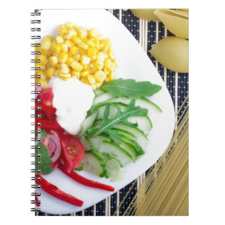 Plato vegetariano de verduras crudas y de la cuaderno