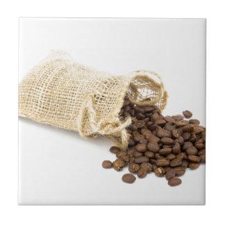 Poca harpillera con los granos de café azulejo