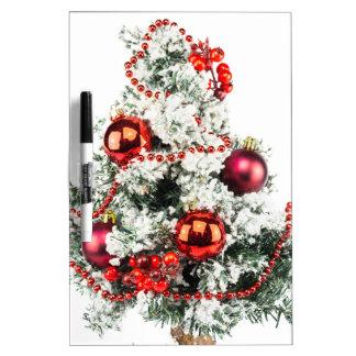Poco árbol de navidad adornado con las chucherías pizarra blanca
