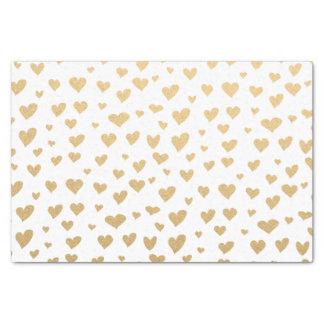 Pocos corazones del oro en fondo blanco como la papel de seda