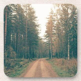 Posavasos Camino de tierra de Brown entre los árboles con