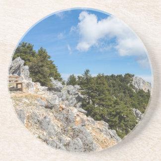 Posavasos De Arenisca Bench en la montaña rocosa con los árboles y el