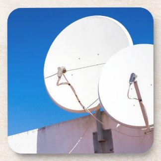 Posavasos Dos antenas parabólicas blancas en la pared de la
