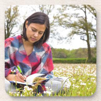 Posavasos Escritura de la mujer en prado con las flores de