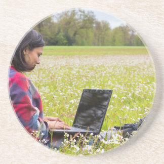 Posavasos Mujer que se sienta con el ordenador portátil en