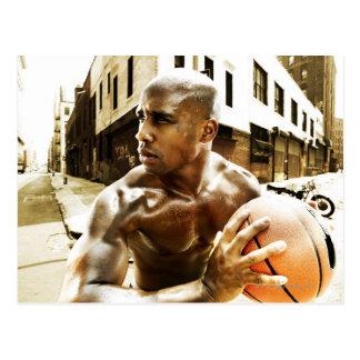 Postal Hombre joven que lleva a cabo baloncesto