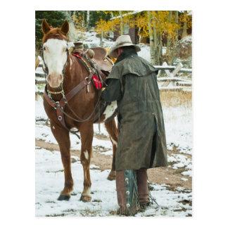 Postal Hombre que pone la silla de montar en caballo