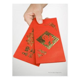 Postal Mano que sostiene el sobre chino del dinero