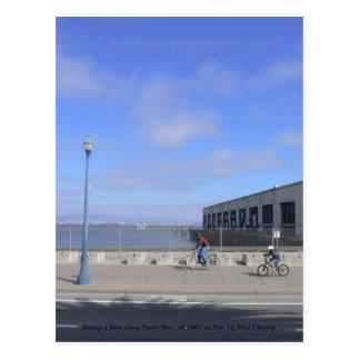 Postal Montando una bici a lo largo de los embarcaderos…