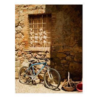 Postal Monte en bicicleta delante de una pared,